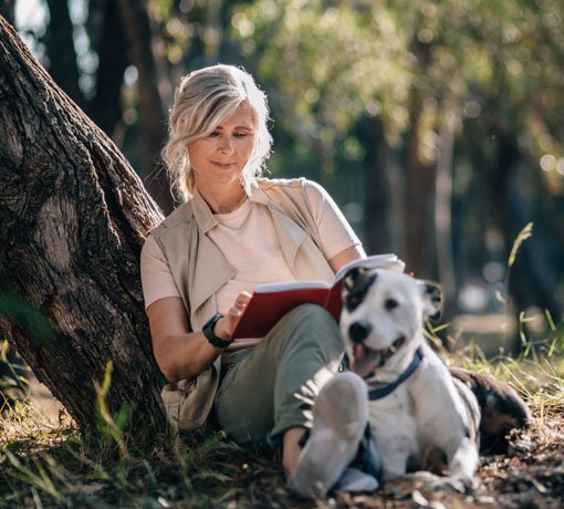 Woman reading outdoors with dog