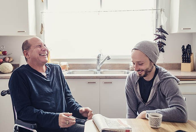 Two men laughing at kitchen table